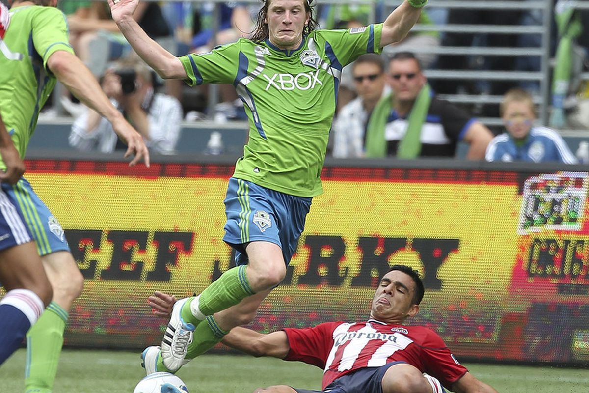 SEATTLE - AUGUST 13:  Erik Friberg #8 of the Seattle Sounders FC sails over Michael Umana #4 of Chivas USA at CenturyLink Field on August 13, 2011 in Seattle, Washington. (Photo by Otto Greule Jr/Getty Images)