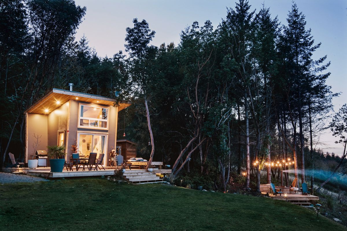 A tiny house with lights on inside and on its roof glows amid a forest setting. A separate deck with a hot tub is also lit up by string lights.