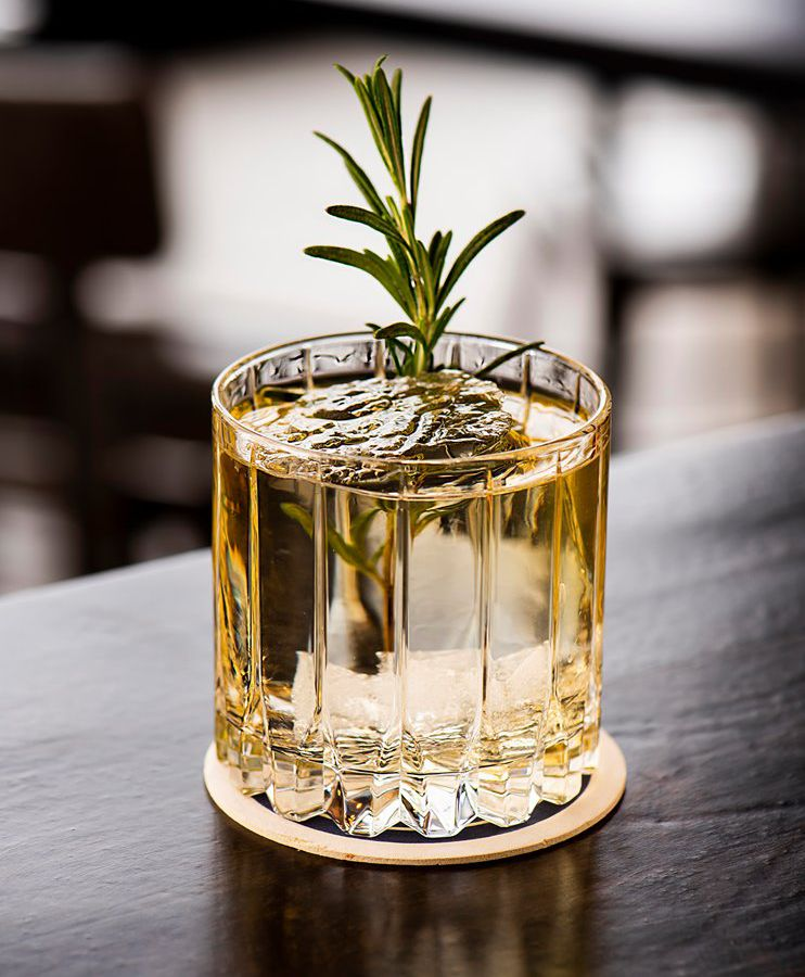 A lowball glass with clear ice, golden beverage and garnished with a sprig of rosemary