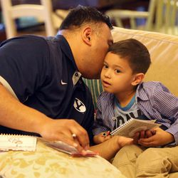 Kalani Sitake whispers in his son KK's ear while playing a game in Provo on Friday, March 11, 2016.