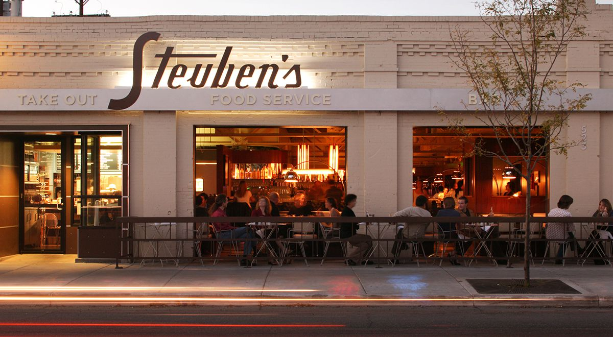 A photo of the exterior of Steuben's showing the large Steuben's sign and customers on the patio