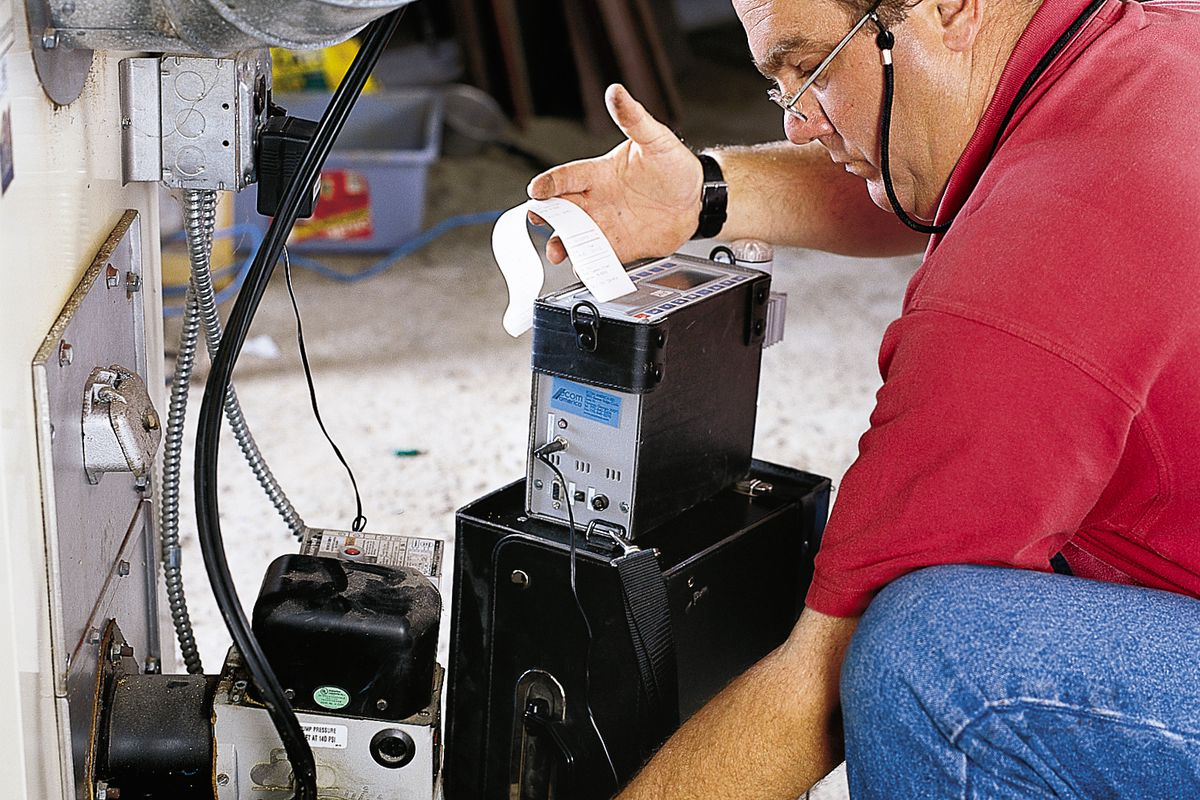 Person checking to see if a furnace is in good condition during an annual furnace cleaning.