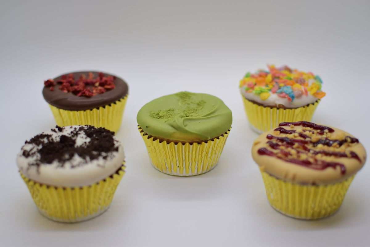 Five mochi cupcakes with various colorful toppings and yellow cupcake liners