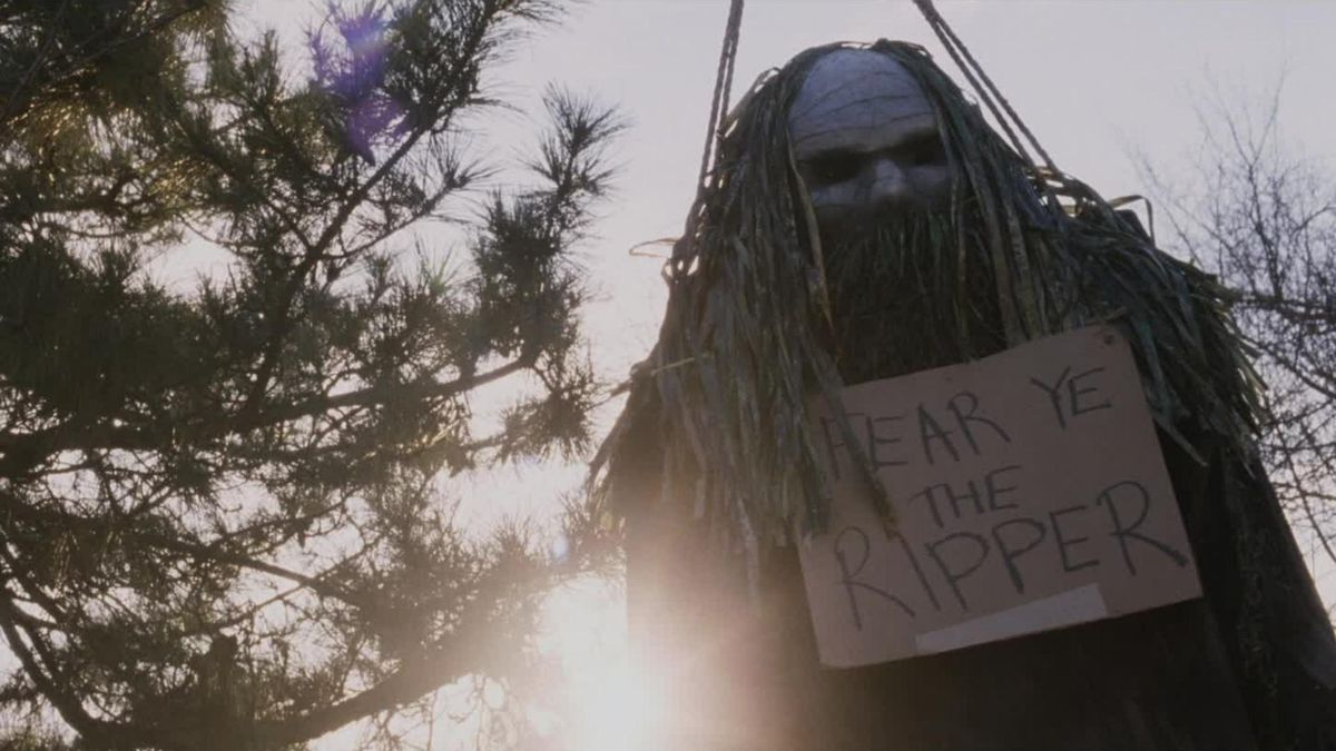 """A ghoulish masked effigy with a cardboard sign reading, """"Fear Ye The Ripper"""" in My Soul To Take"""