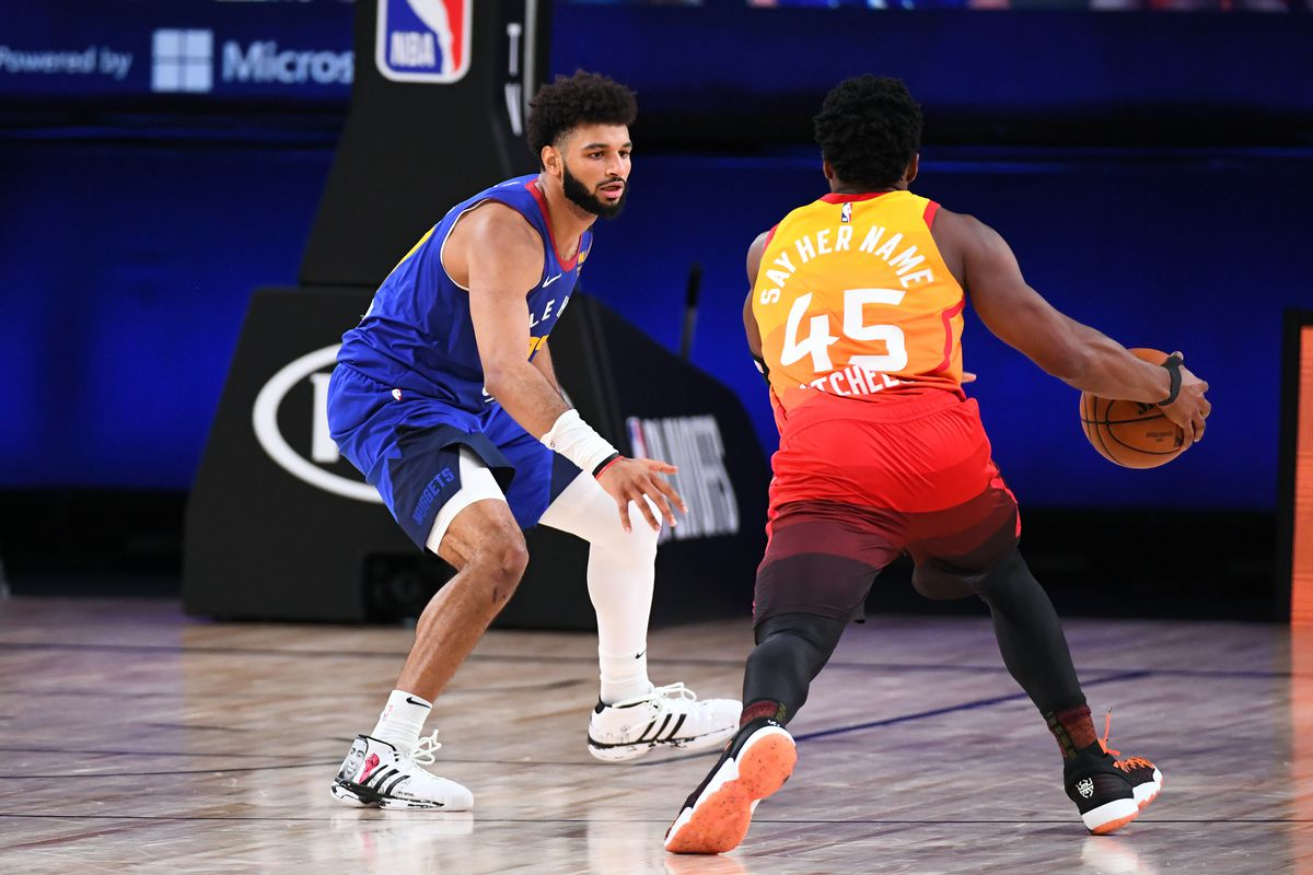 Donovan Mitchell of the Utah Jazz handles the ball while Jamal Murray of the Denver Nuggets plays defense during Round One Game Six of the NBA Playoffs on August 30, 2020 at The AdventHealth Arena at ESPN Wide World Of Sports Complex in Orlando, Florida.