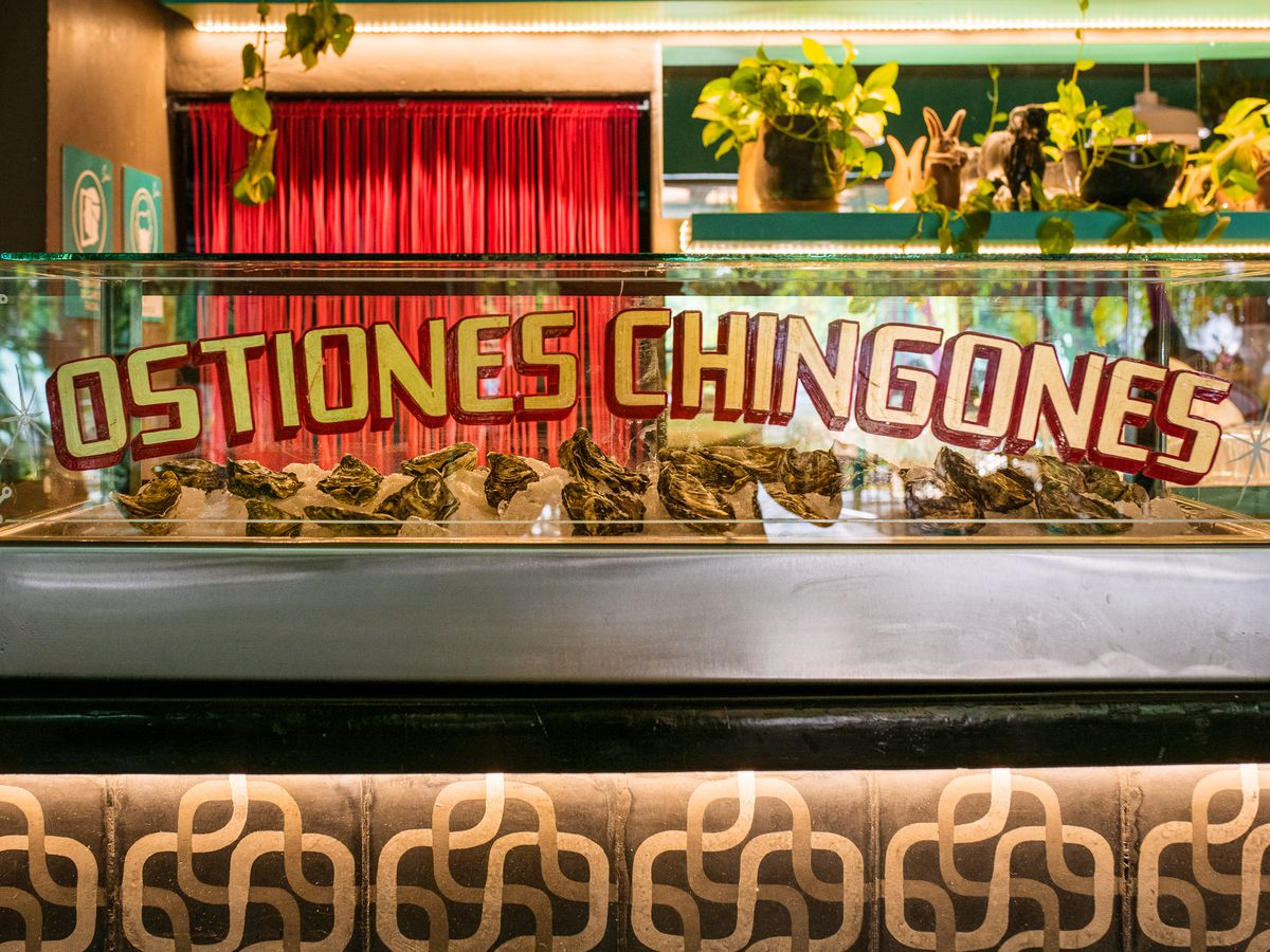 """A long oyster bar behind glass that says """"ostiones chingognes"""" in painted letters."""