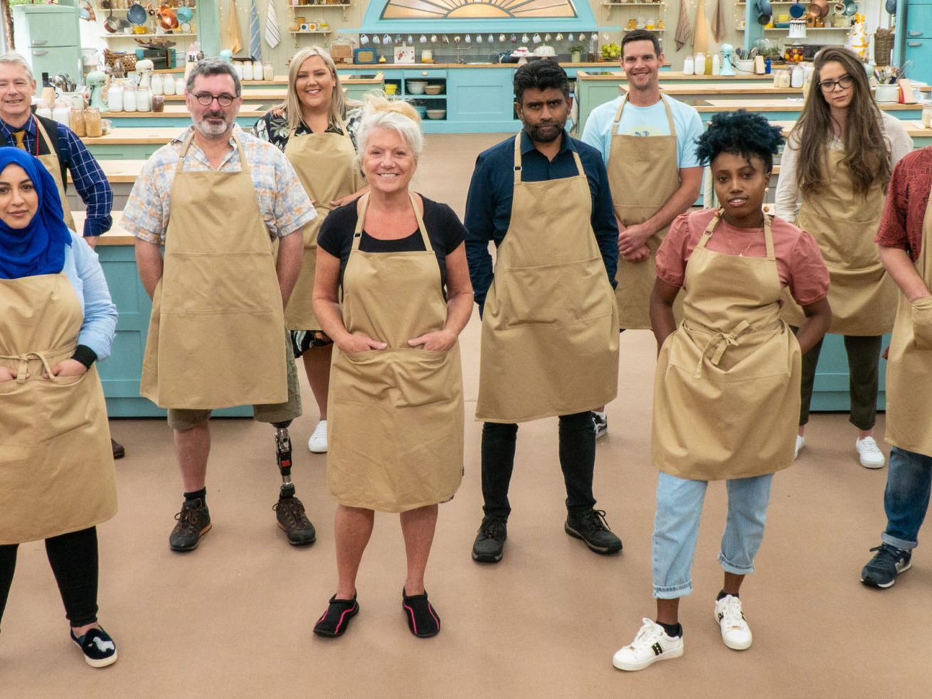 The contestants of the 11th season of the Great British Bake Off, wearing beige aprons, in the tent