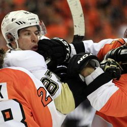 Philadelphia Flyers Claude Giroux, left, holds on to Pittsburgh Penguins Sidney Crosby as Kimmo Timonen, right, lands a punch to Crosby's jaw during the first period of Game 3 in a first-round NHL Stanley Cup playoffs hockey series, Sunday, April 15, 2012, in Philadelphia.