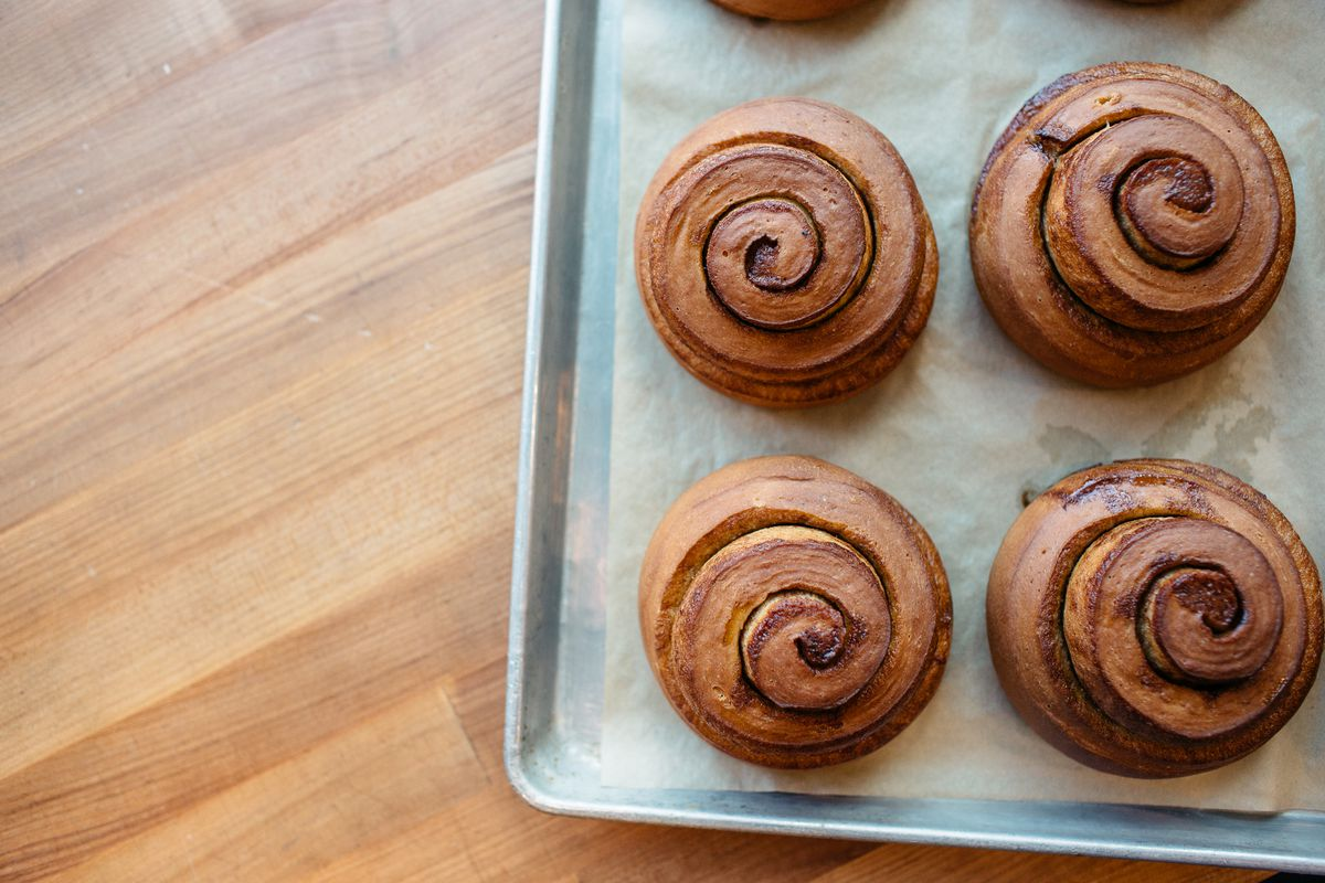 A tray of cinnamon rolls on a wood table.