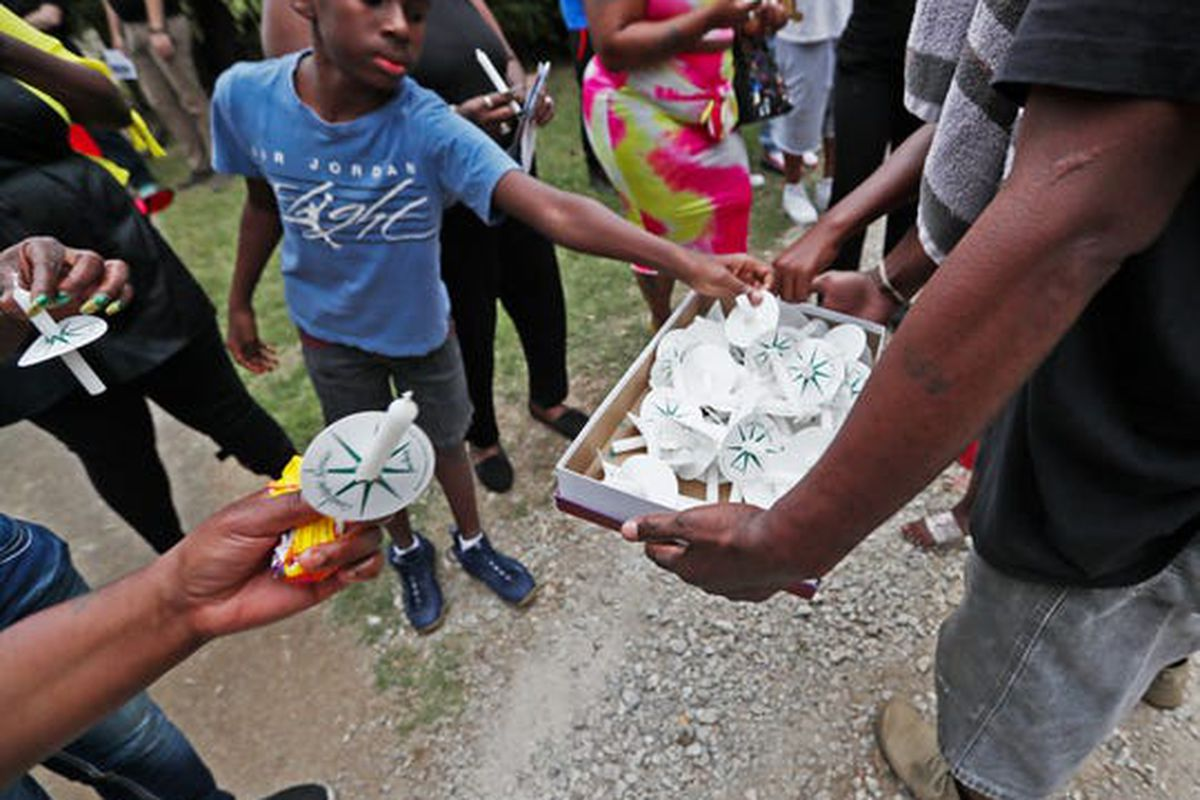 Candles are passed out as community members gather near the Frayser home of Brandon Webber on Friday, June 14, 2019.