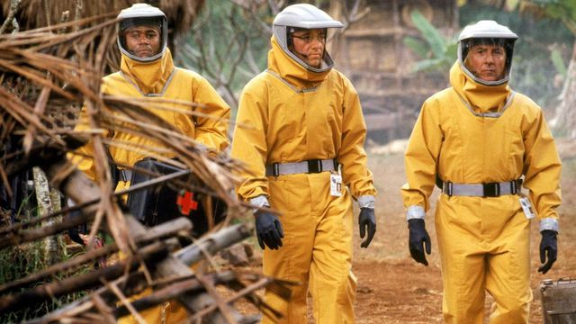 three scientists in hazmat suits in a jungle