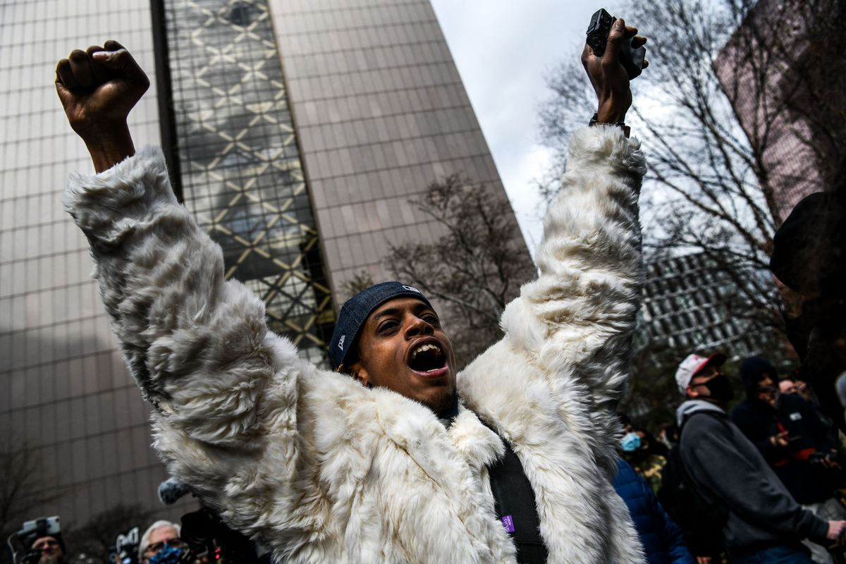A Black man in a white fur coat raises both his arms in the air, while shouting, seemingly in joy.