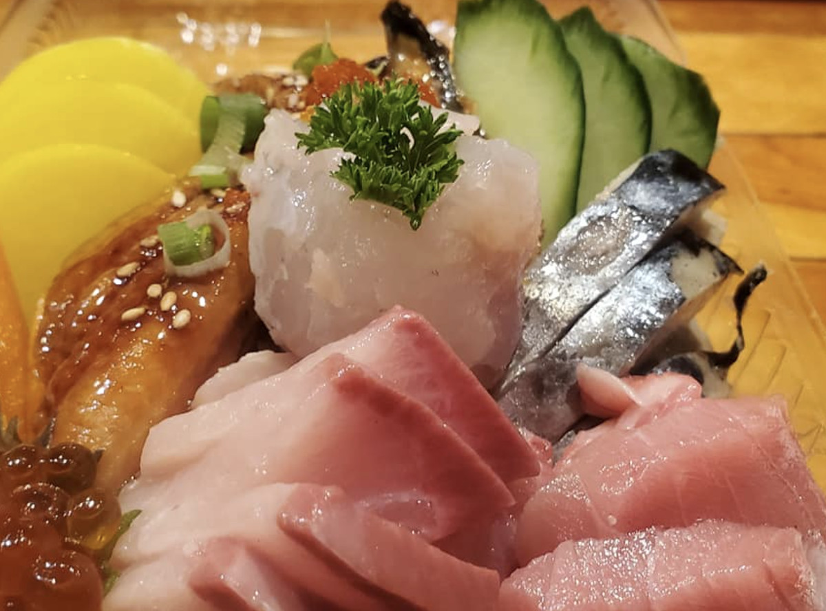 A collection of sashimi, showing yellowtail, roe, and sliced cucumber