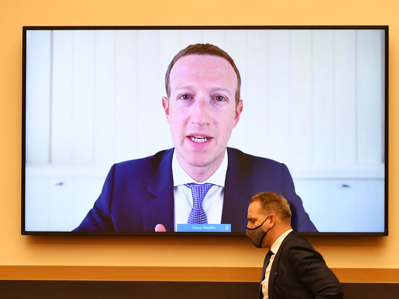Mark Zuckerberg's face on a large television screen.