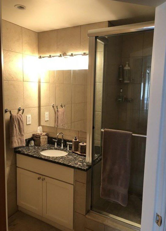 A small bathroom with a sink next to a glass-door shower.