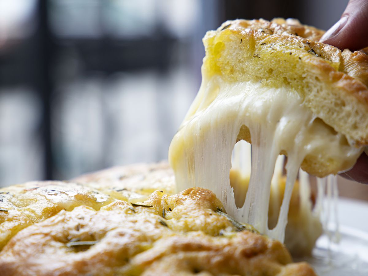 A hand pulls away a triangle of taleggio-stuffed focaccia bread at Fox and the Knife in South Boston