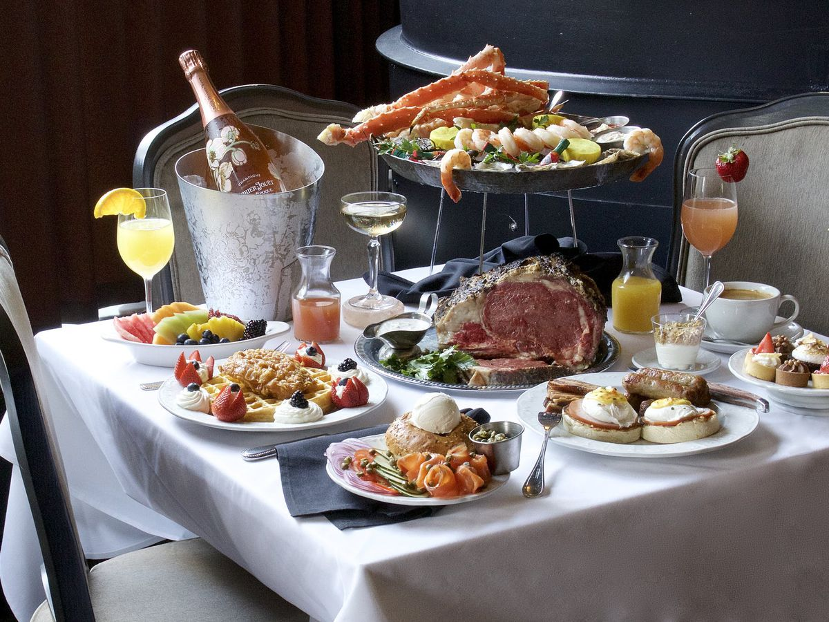 A variety of brunch dishes and drinks, prime rib, a bottle of wine in a bucket, and crab legs spread out on a table.
