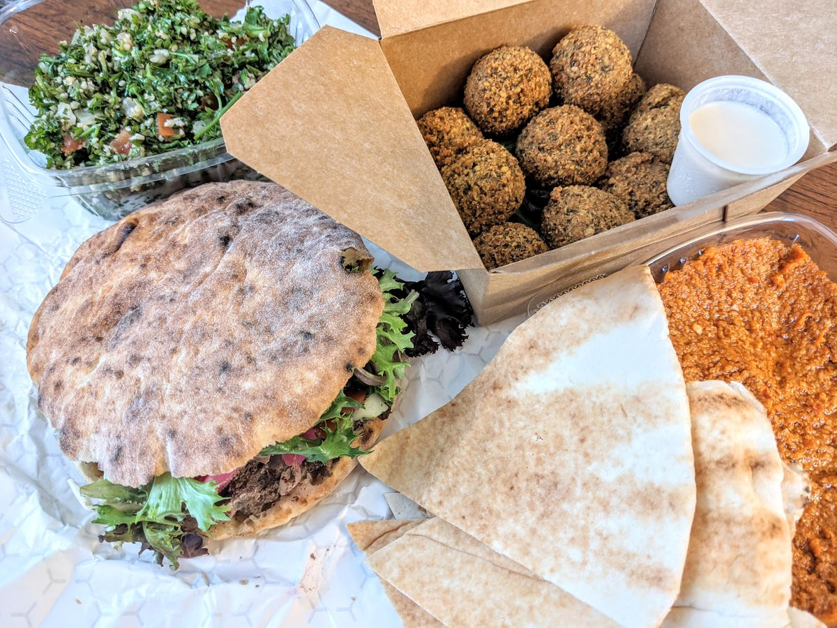 Near-overhead view of a table full of Middle Eastern delivery food —a pita stuffed with meat, greens, and pickles; falafel with a tiny cup of tahini; tabbouleh; muhamara; and pita.
