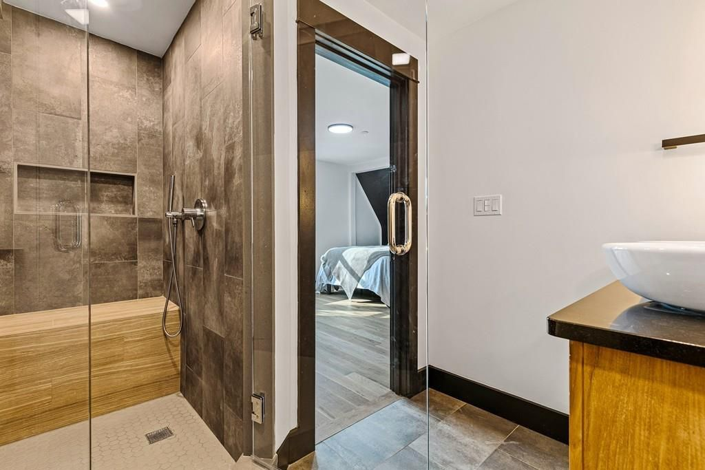 The entryway to a bathroom with basin sinks and a steam shower.