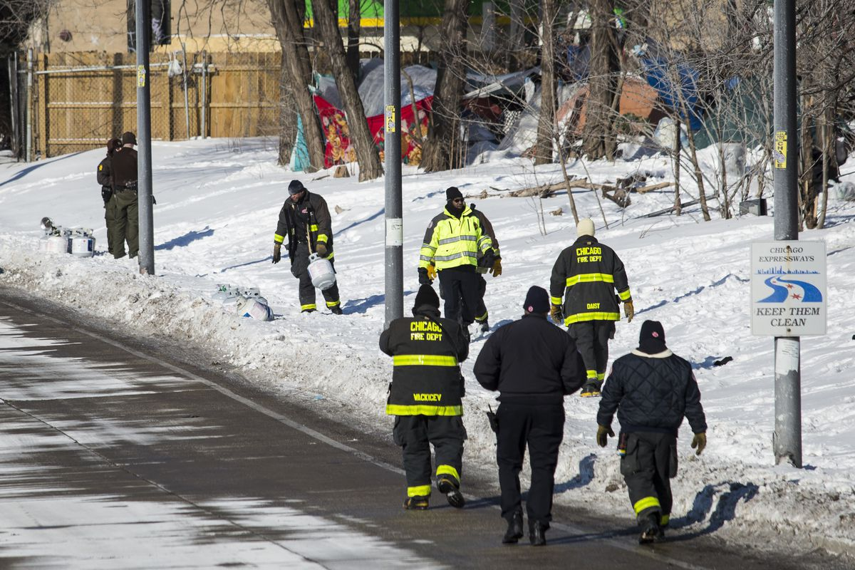 Chicago Fire Department firefighters remove propane tanks from the homeless encampment near Roosevelt Road and South Desplaines Street, overlooking the Dan Ryan Expressway, Wednesday afternoon, Jan. 30, 2019.   Ashlee Rezin/Sun-Times
