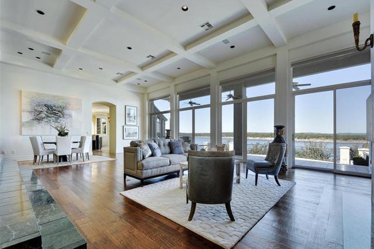 Large contemporary living room with wood floors and white furniture and lake visible through big windows