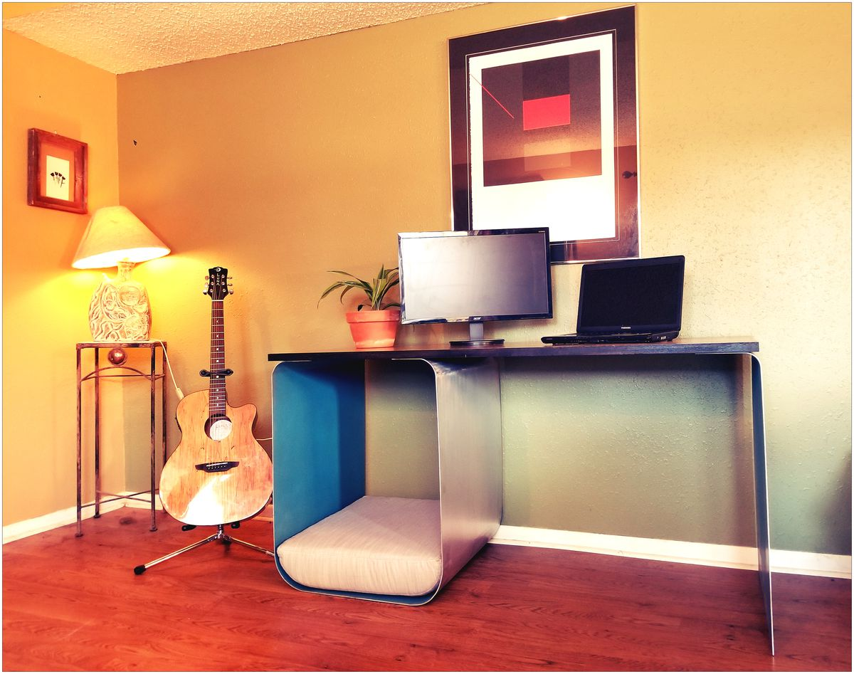 Interior photo of a simple desk with a metal cube serving as support and dog cubby on one end.