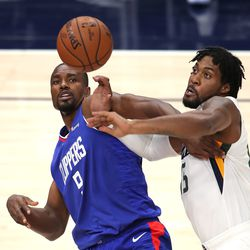 LA Clippers forward Serge Ibaka (9) and Utah Jazz center Derrick Favors (15) battle for the ball as the Utah Jazz and LA Clippers play in an NBA basketball game at Vivint Smart Home Arena in Salt Lake City on Friday, Jan. 1, 2021.