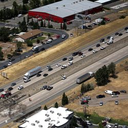 Southbound traffic crawls around the scene of a fatal plane crash on I-15 as northbound is closed in Riverdale on Wednesday, July 26, 2017. All four people on board died.