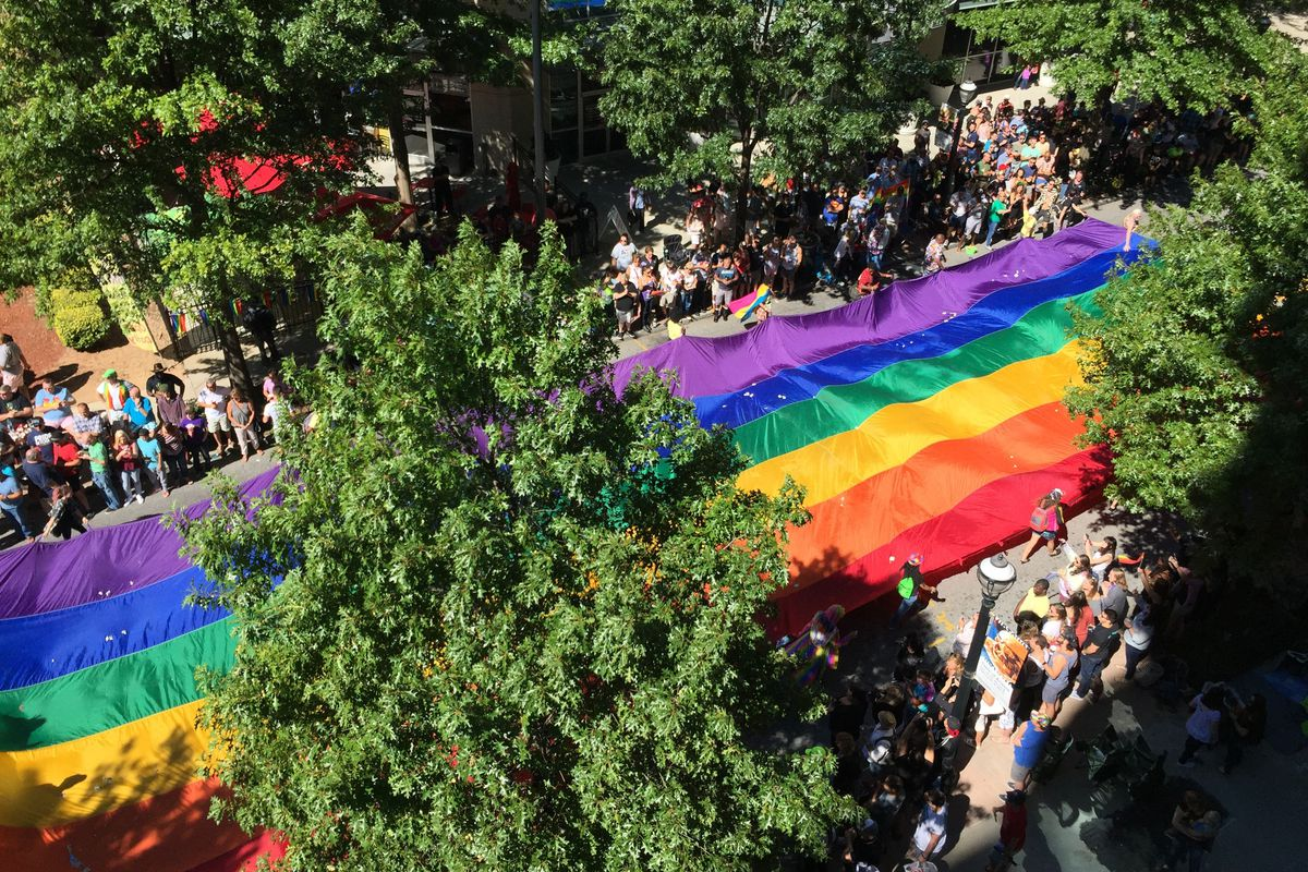 A large rainbow flag is carried down Peachtree Street in Midtown, seen from above.
