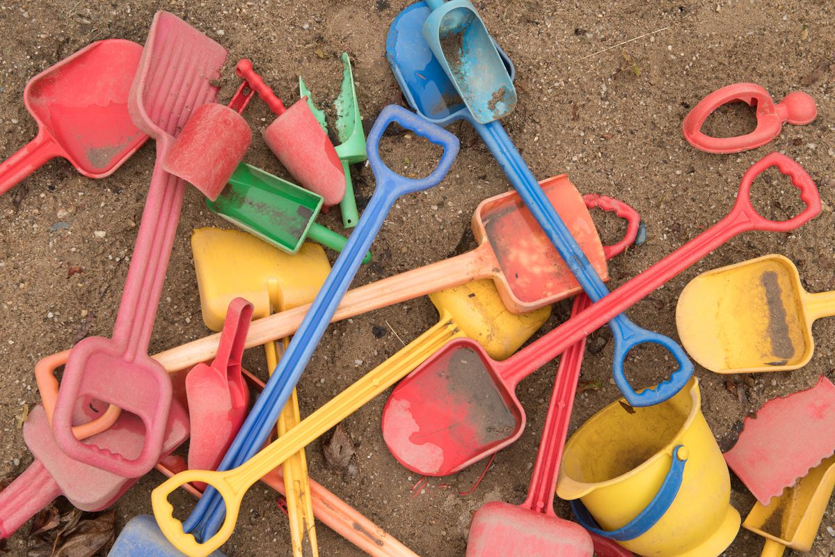 Red, yellow, blue and green toy shovels and a bucket in the sand.