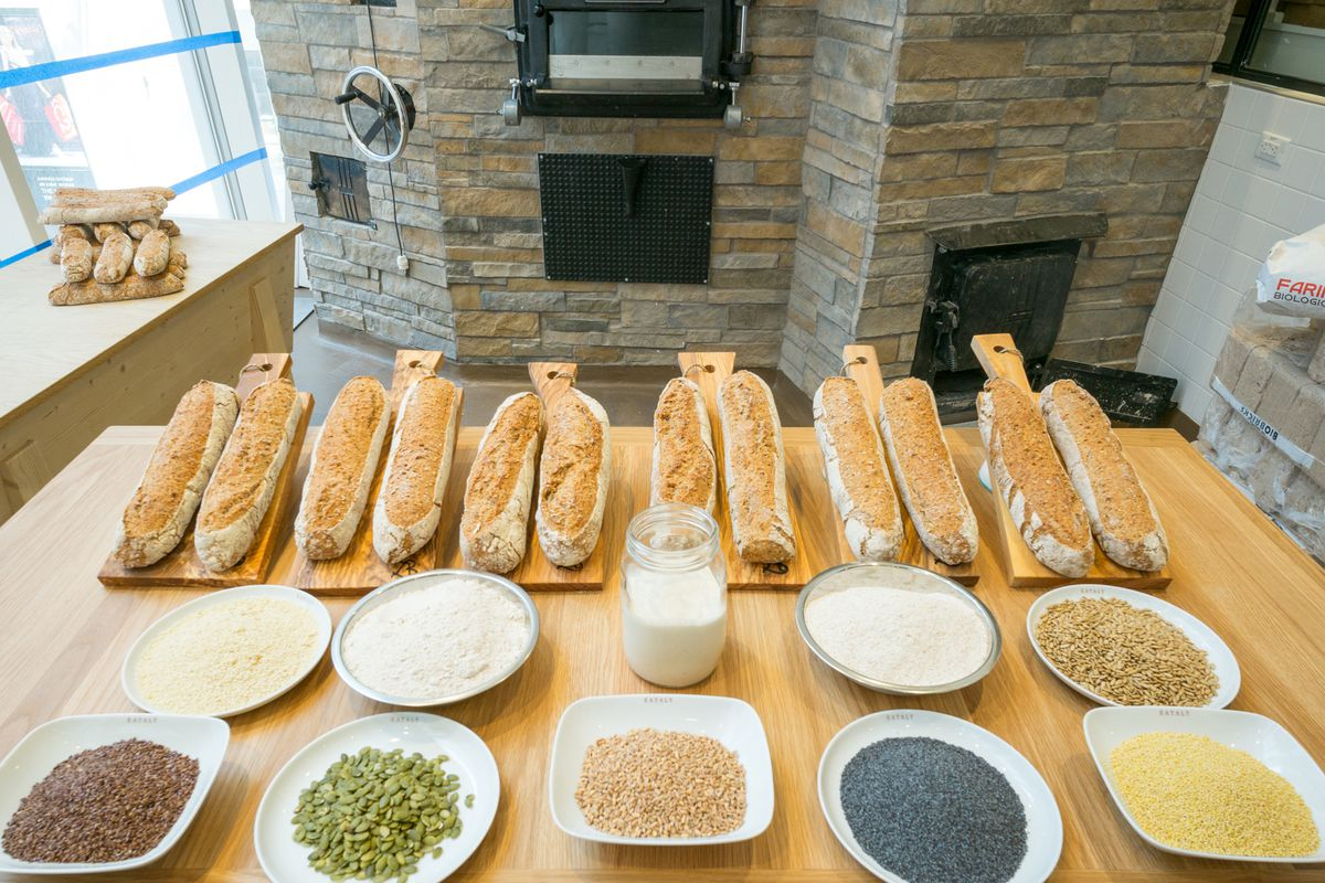 A row of loaves can be seen resting on cutting boards on a wooden table. Also on the table are white plates with a variety of grains