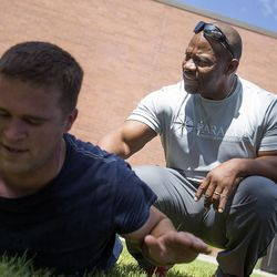 Ron Williams, a nondenominational Christian pastor, right, assists Jeremy Ware through back muscle exercises with a group of Utah National Guard members at their headquarters on Thursday, Aug. 14, 2014.