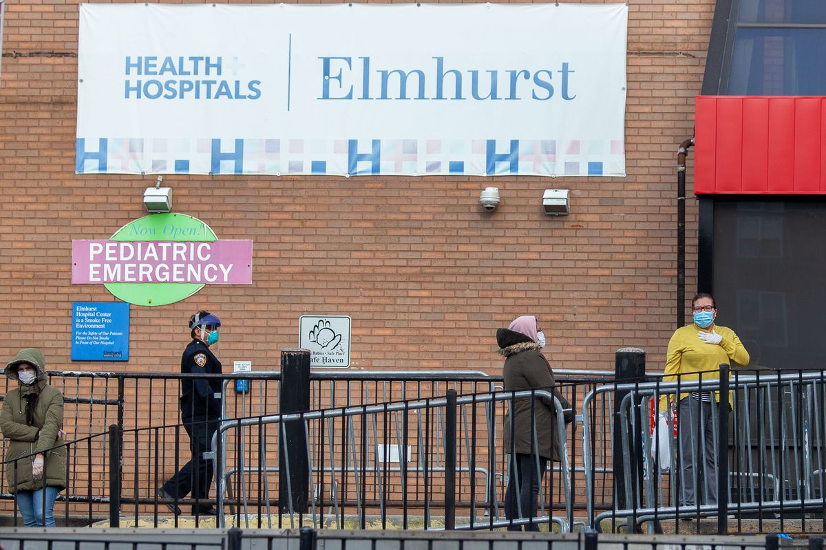 A hospital security officer helps oversee a coronavirus testing line at the Elmhurst Hospital Center.