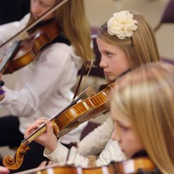 Gifted Music School orchestra student Karen Ferry, center, practices in Salt Lake City on April 13.