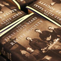 """Books are stacked nearby as co-editors of """"The First Fifty Years of Relief Society,"""" released by the LDS Church on the Church Historian's Press, are interviewed at the Relief Society Building in Salt Lake City, Monday, Feb. 22, 2016."""