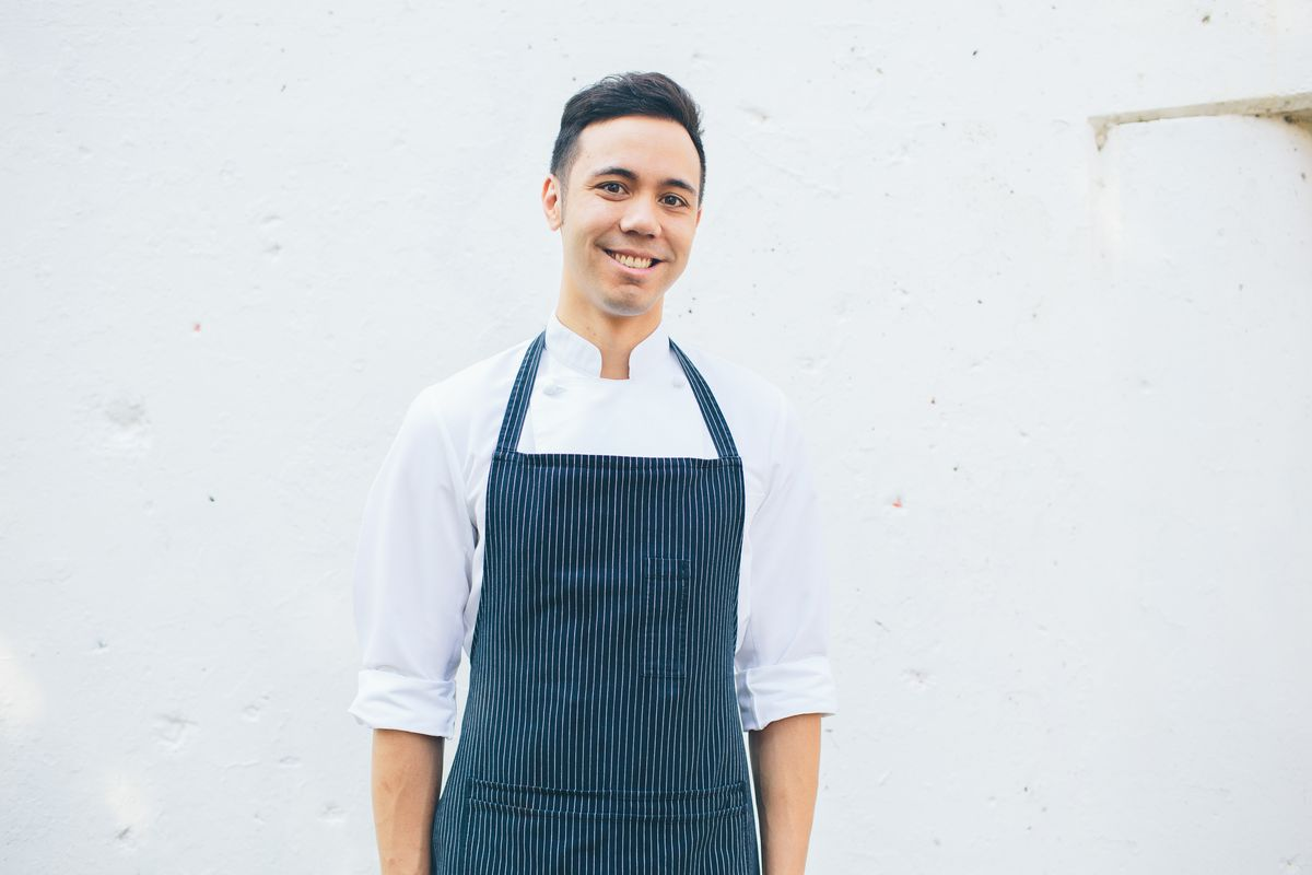 A chef in a white shirt with a dark apron who is smiling.