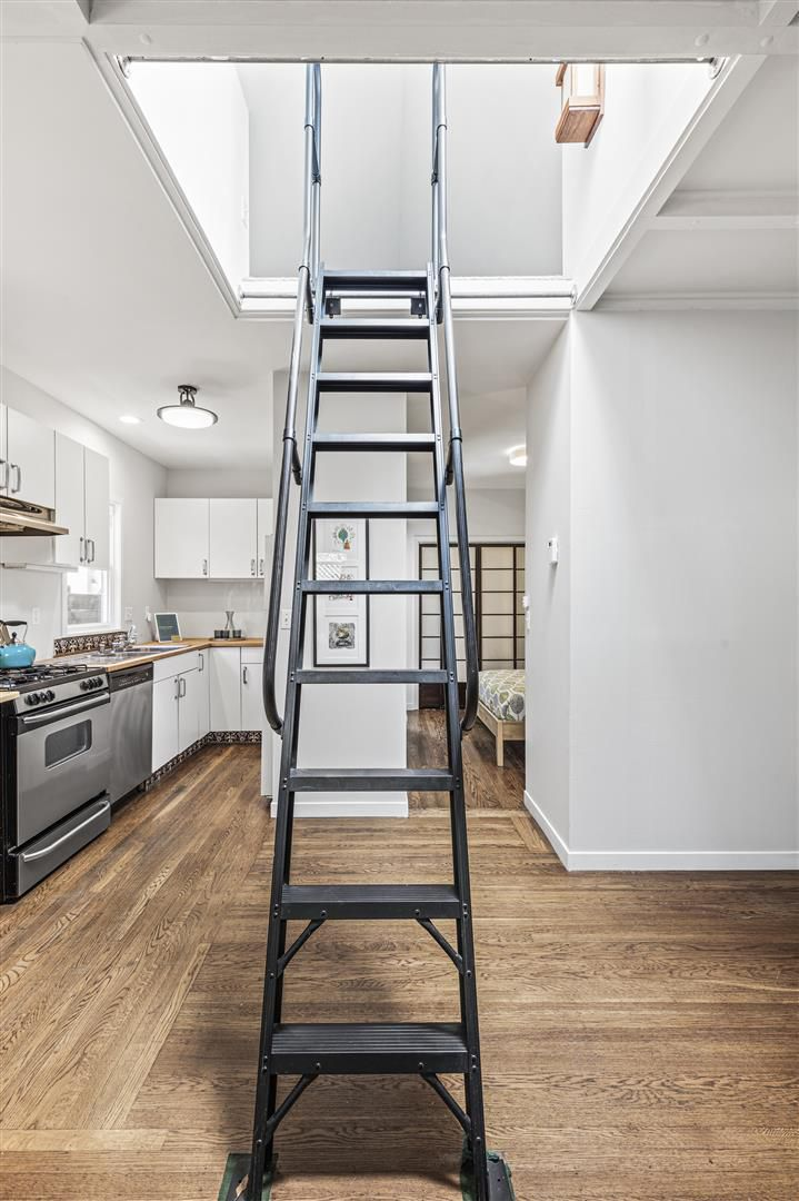 A black metal ladder leads up to the attic loft space.