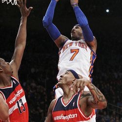 New York Knicks' Carmelo Anthony (7) shoots over Washington Wizards' James Singleton (3) and Kevin Seraphin (13) during the first half of an NBA basketball game Friday, April 13, 2012, in New York.