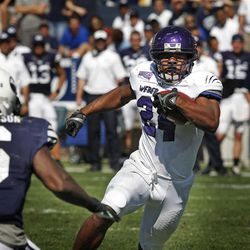 Weber State running back Josh Booker (24) tries to elude BYU's Jordan Johnson (6) Saturday afternoon.