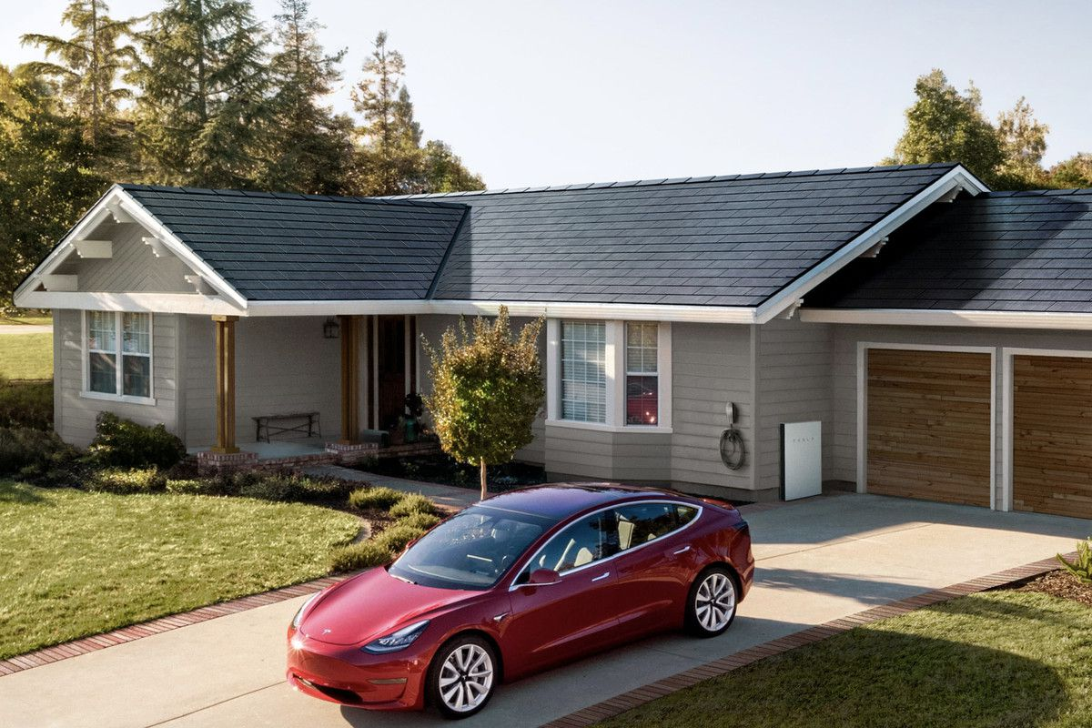 Car parked in driveway of home with solar powered roof tiles on a single-level house, with a red car in the driveway.