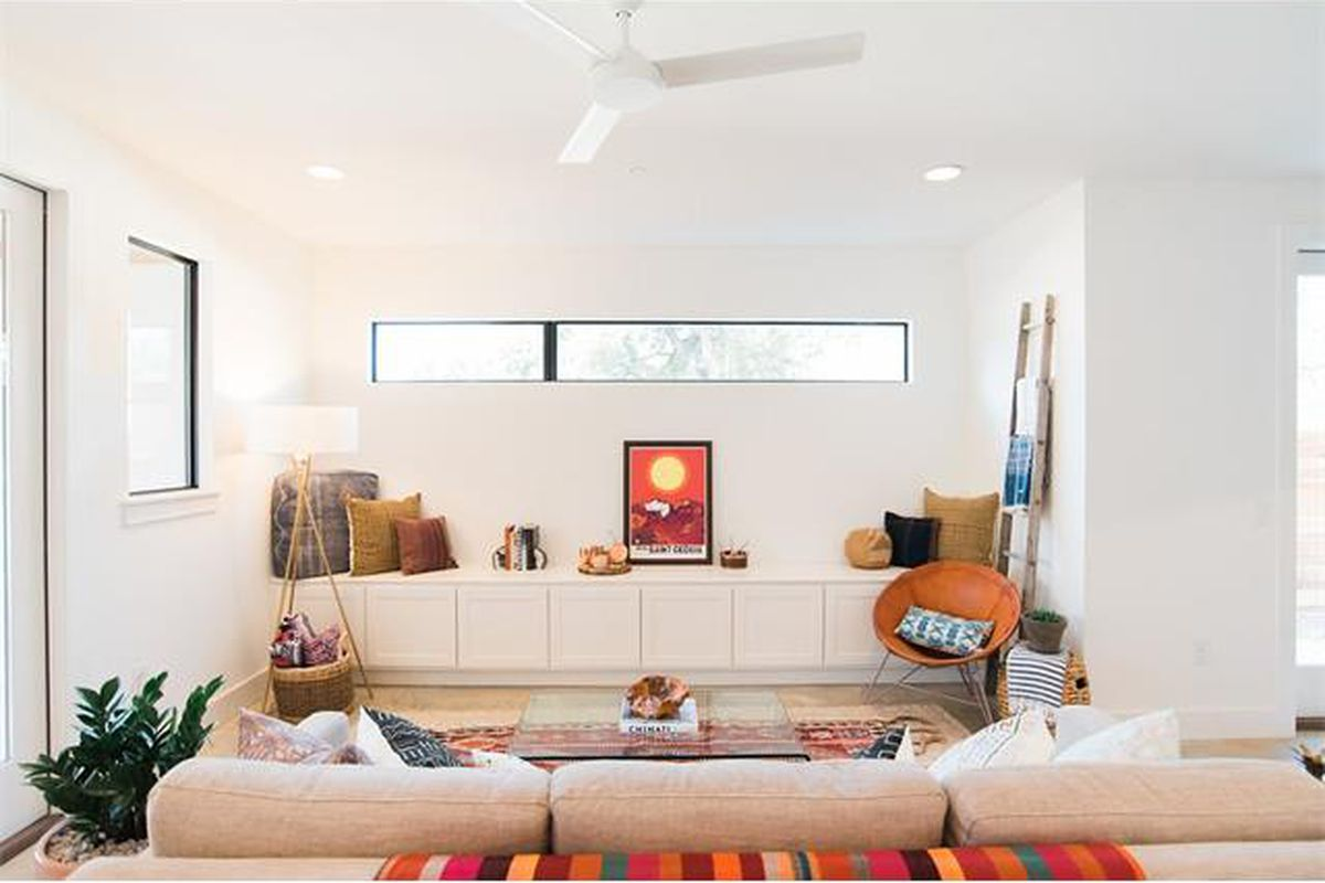 A white living room with white couch, clerestory and picture window, new, contemporary