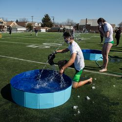Mason Kim shakes his head after plunging into a wading pool with snow for St. Patrick High School's version of the Polar Plunge.