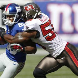 New York Giants wide receiver Victor Cruz (80) is tackled by Tampa Bay Buccaneers' Quincy Black (58) during the first half of an NFL football game on Sunday, Sept. 16, 2012, in East Rutherford, N.J.