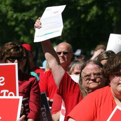 """Michele Orr holds up her new contract offer as she rallies with other teachers from Ogden City School District, their families and others from surrounding districts, to protest during a rally in Ogden Thursday, July 14, 2011, against the """"take it or leave it"""" contract issued to Ogden teachers several weeks ago."""