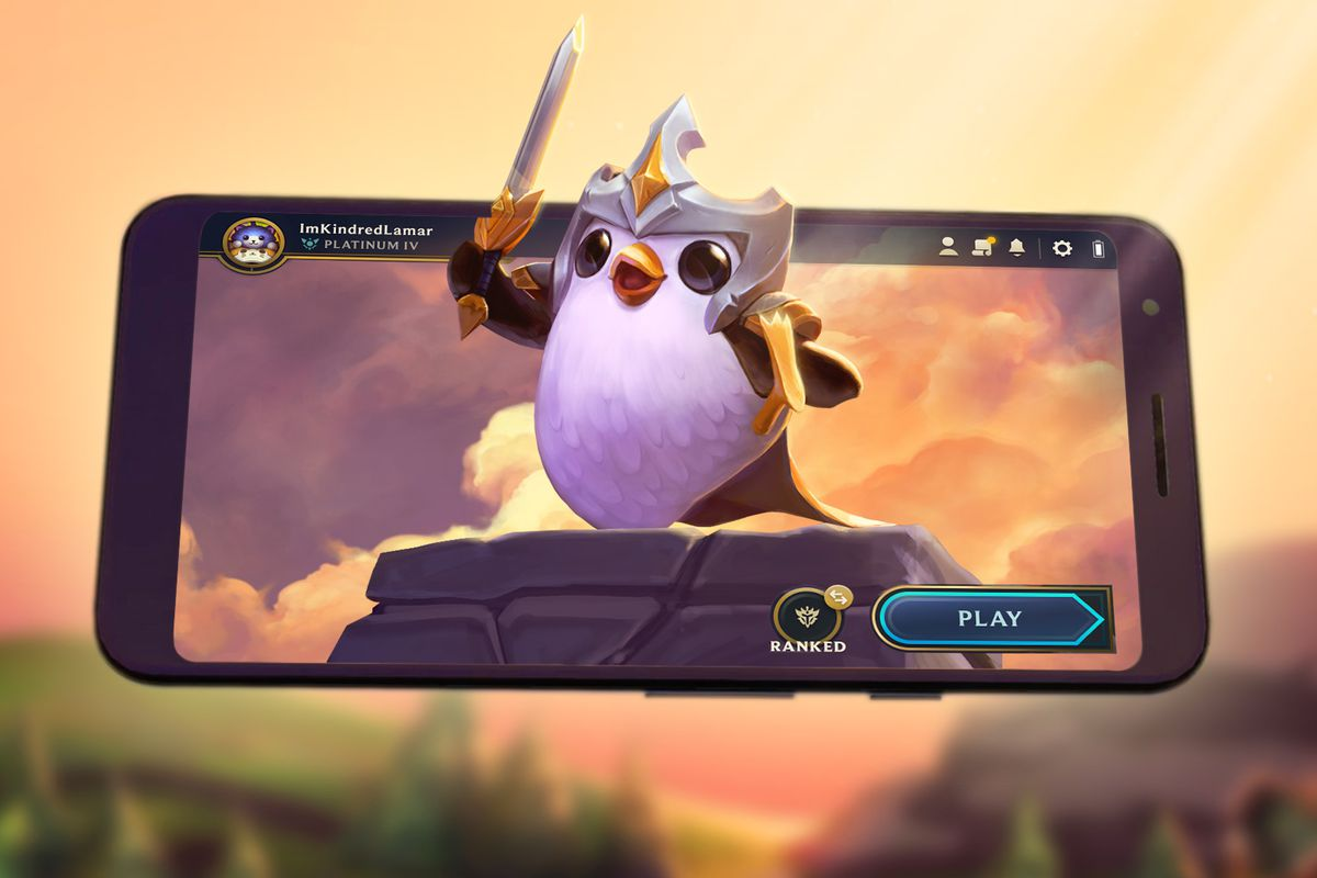 A small penguin holds a sword in front of a phone that is playing Teamfight Tactics