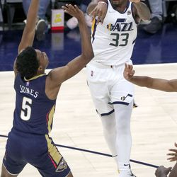 Utah Jazz forward Elijah Hughes (33) passes the ball over New Orleans Pelicans guard Nickeil Alexander-Walker (6) during a preseason NBA game at the Vivint Smart Home Arena in Salt Lake City on Monday, Oct. 11, 2021. The Jazz won 127-96.