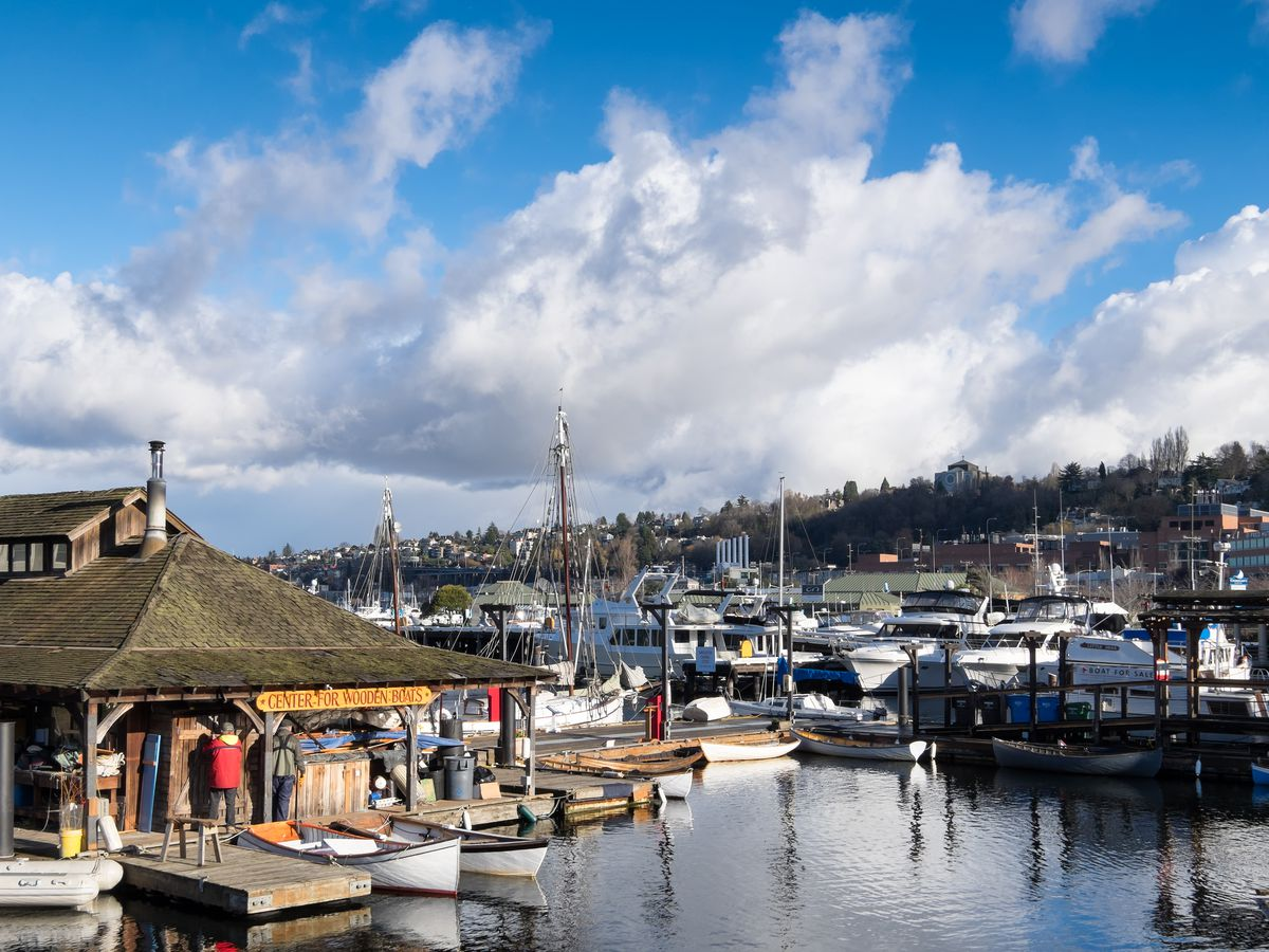A boat marina with a pier and many boats sitting on the water.