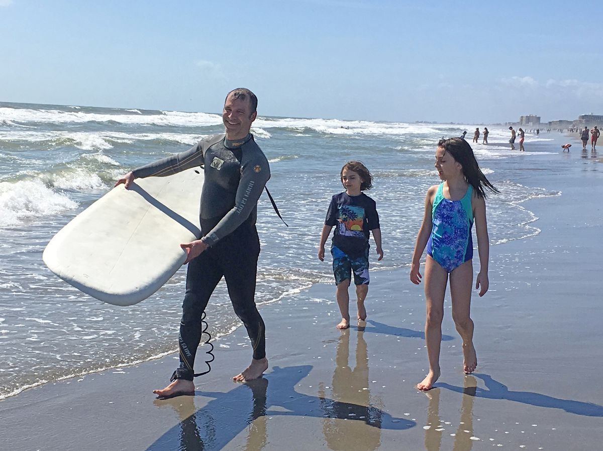 Matthew Lipinski, with his daughters at the beach. Last month he used a life ring to help rescue three people at a beach in Michigan.