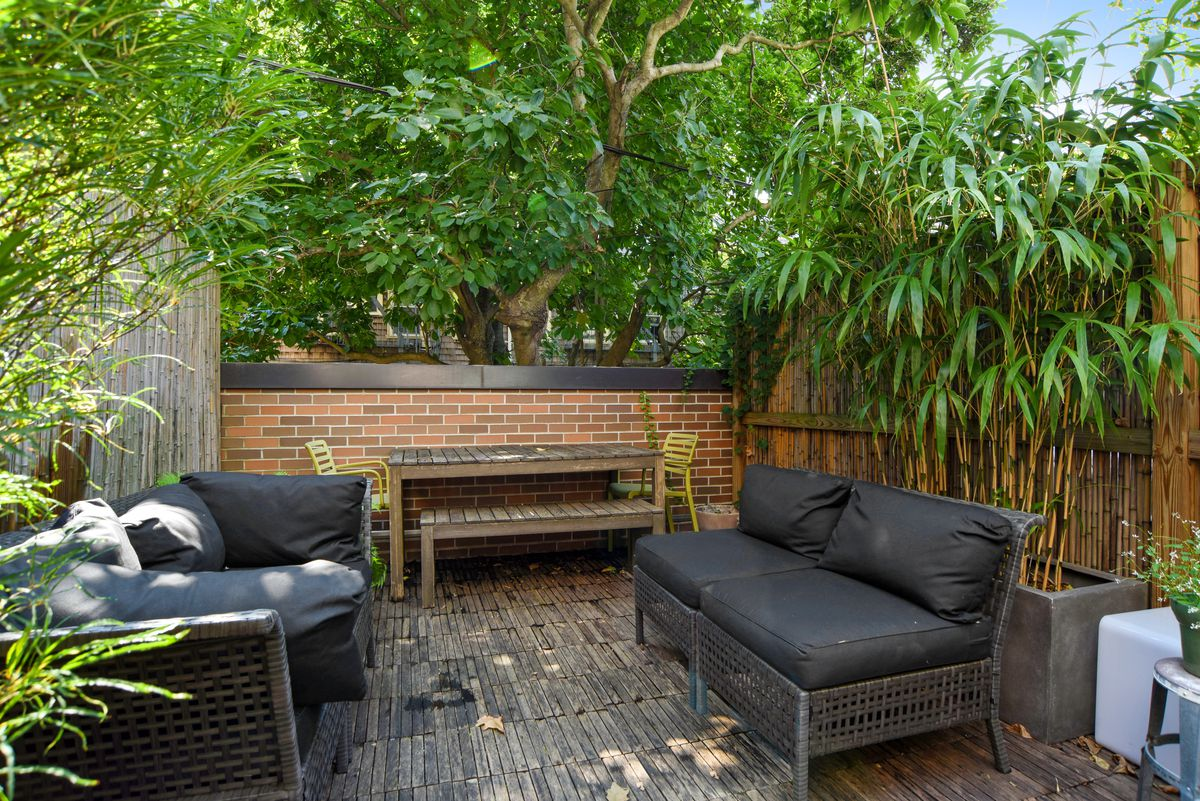 A garden with black couches, exposed brick, and several planters.