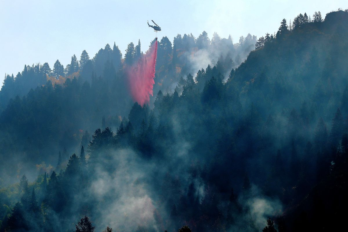 A helicopter drops retardant to battle the Pole Creek fire in Woodland Hills on Friday, Sept. 21.